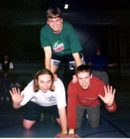 Simon Greenway from England and Brian Lecy from S.D. wave while Gilby poses on top.